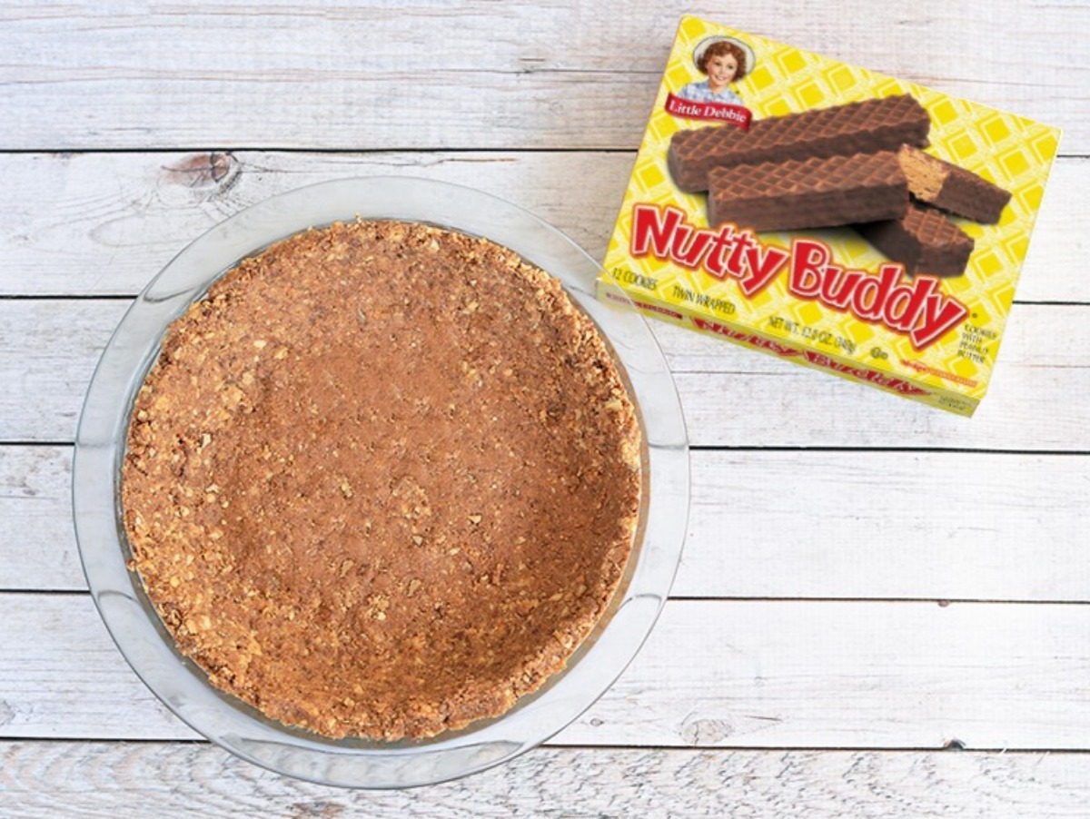 Nutty Buddy pie shell crumbs pressed into glass pie dish.